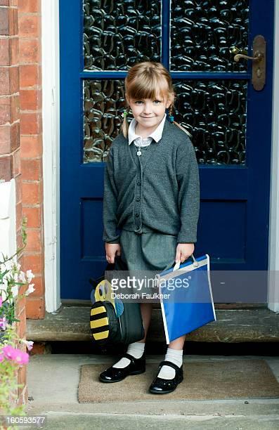 Small girl in school uniform by front door