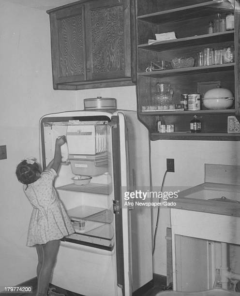 A small girl is something taking in a fridge in her home's kitchen 1942