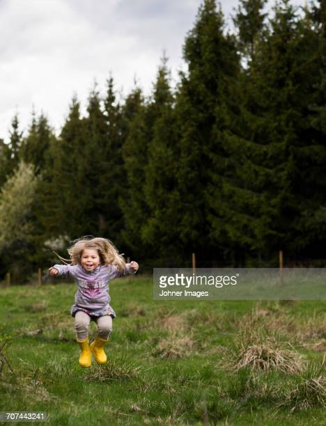 Small girl jumping in forest