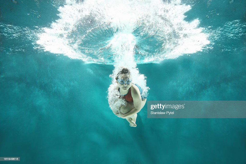 Small girl jumping into the water- underwater view : Stock Photo