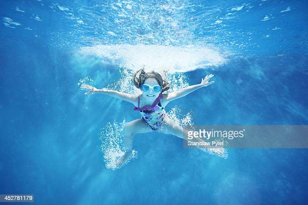 Small girl jumping into water- underwater view