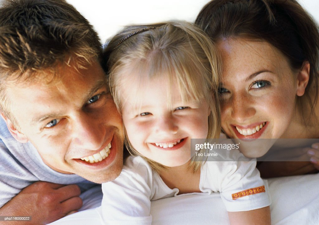 Small girl laying between parents, smiling, close-up : Stockfoto