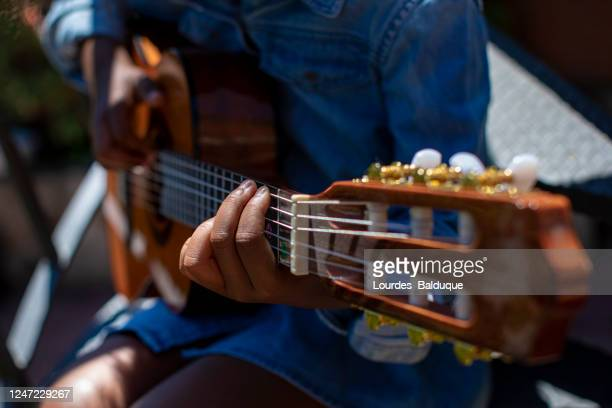 small girl learning to play the guitar - ポップコンサート ストックフォトと画像