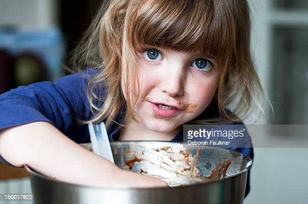 Small girl licking spoon from mixing bowl