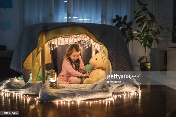 Small girl listening to her teddy bear's heart beat in a tent at home.