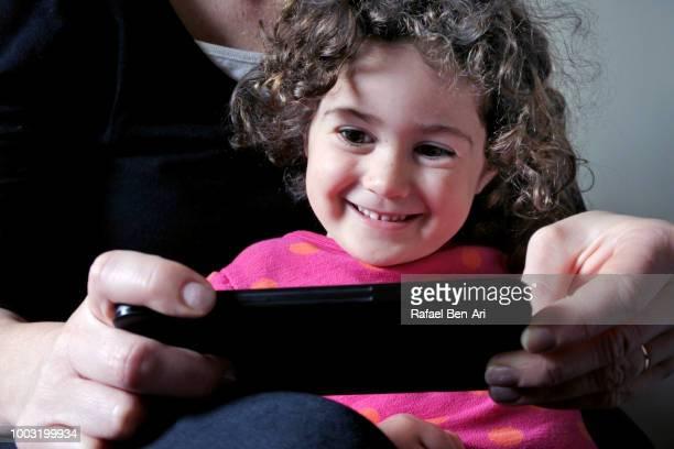 small girl looking at mobile media on a smartphone - rafael ben ari stock-fotos und bilder