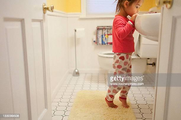 Small girl looking into bathroom sink