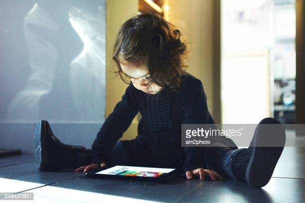 Small girl looking the tablet in the floor