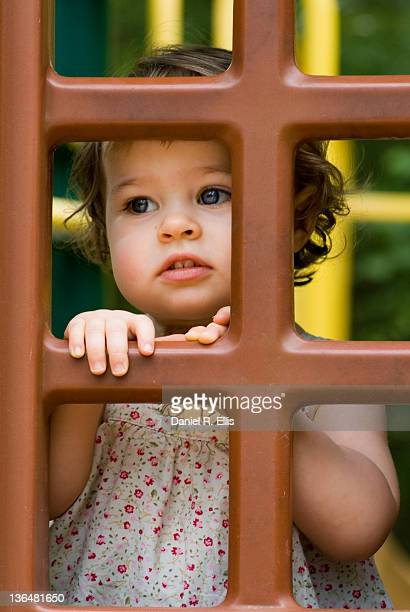 Small girl looking through window
