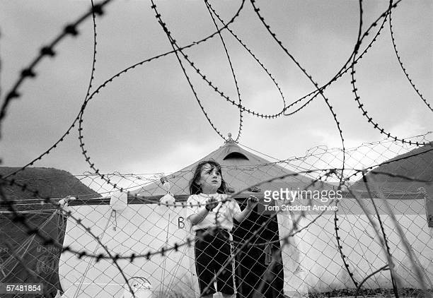 A small girl looks through barbed wire at a refugee camp in Macedonia where thousands of Albanians were kept after being 'ethnically cleansed' from...
