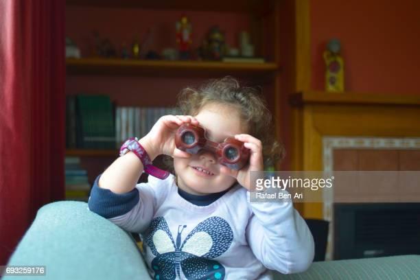 small girl looks through binoculars - rafael ben ari fotografías e imágenes de stock