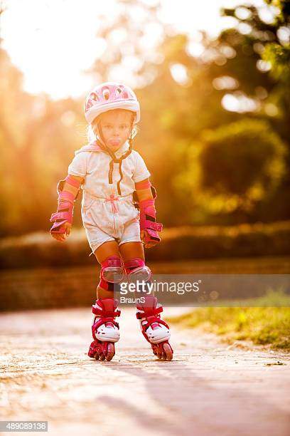 Small girl on rollerblades in the park.