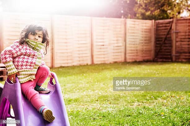 small girl on slide in garden