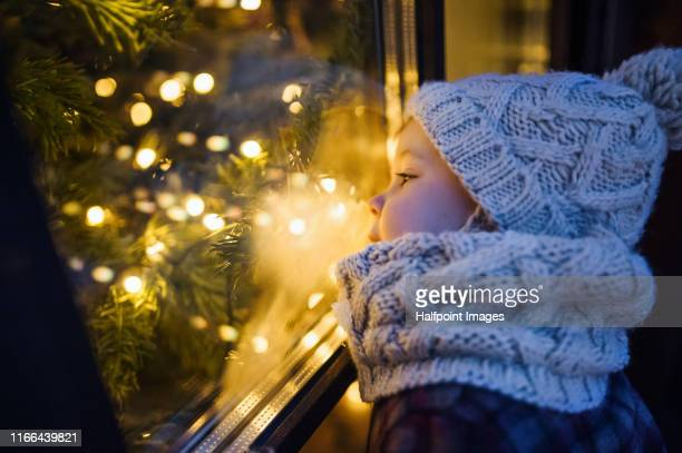 a small girl outdoors in winter, standing on a terrace at christmas time, looking inside through window. - 暦月 ストックフォトと画像