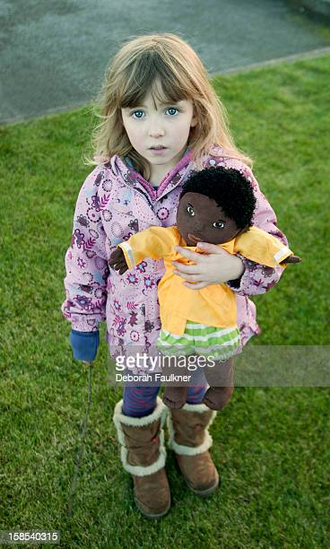 Small girl outside with doll