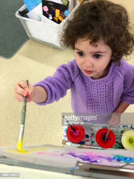 Small girl painting with water colors