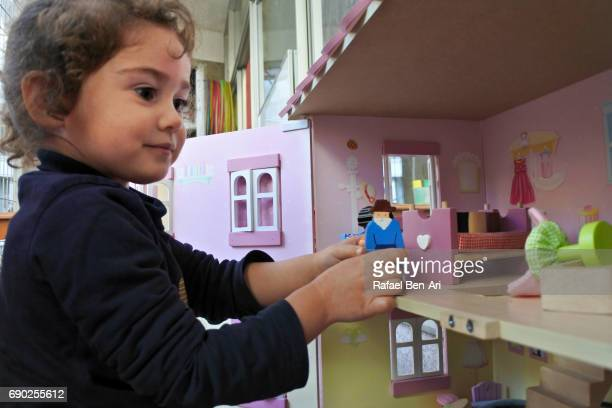 small girl play with a doll house - rafael ben ari stockfoto's en -beelden