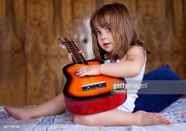 Small girl playing a guitar