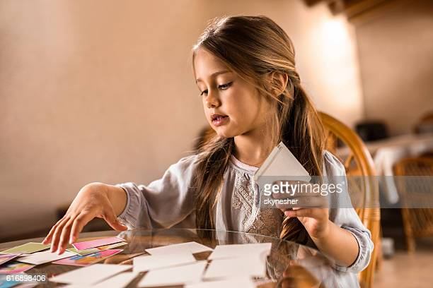 small girl playing card game at the table. - girl mound stock pictures, royalty-free photos & images