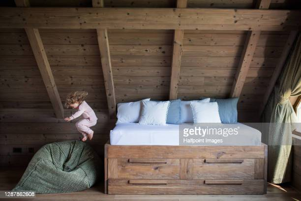 small girl playing in bedroom on holiday, jumping from bed. - sacco photos et images de collection