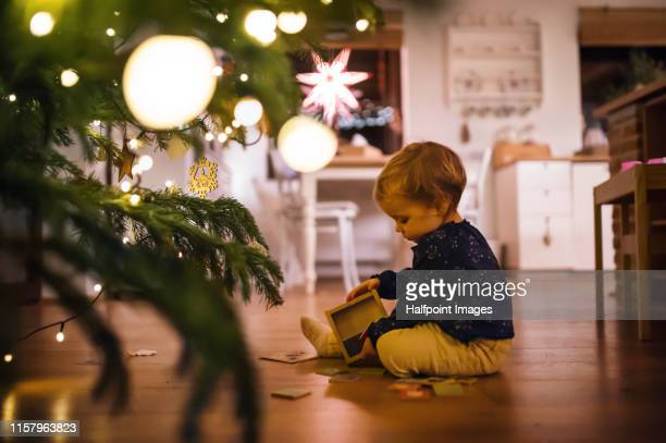 a small girl playing indoors on the floor at christmas time. - dekoration stock-fotos und bilder