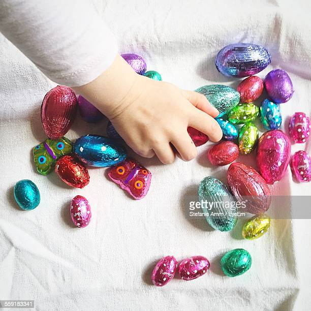 small girl playing with multi colored egg-shaped candies - easter candy stock pictures, royalty-free photos & images