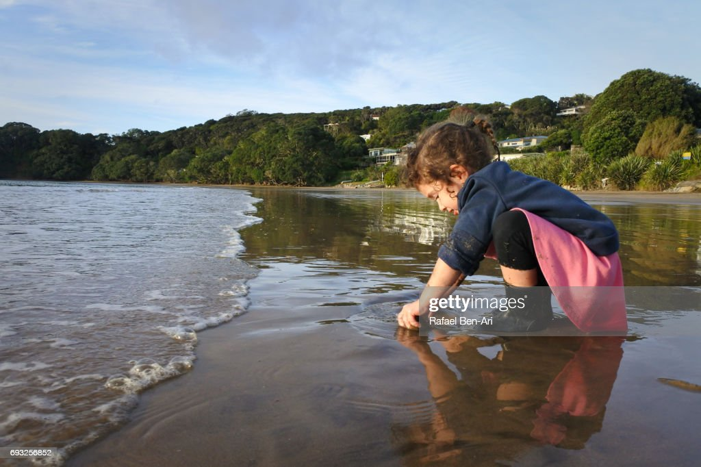Small girl plays with sand on the beach : Stock Photo