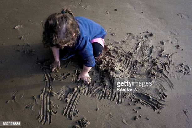 Small girl plays with sand on the beach