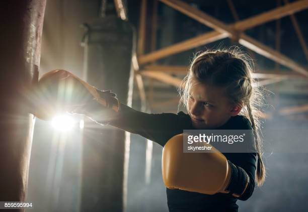 small girl punching a bag on a boxing training in health club. - boxing gloves stock photos and pictures