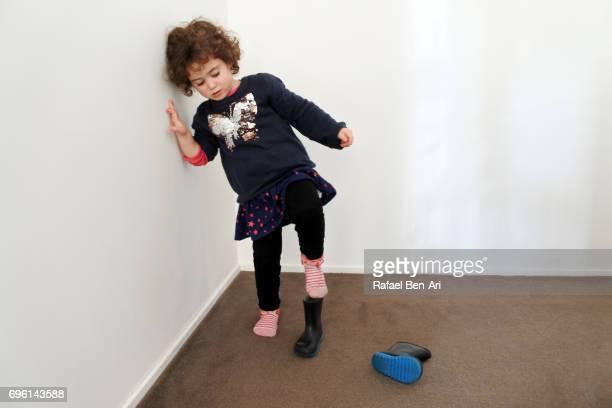 small girl putting on boots - rafael ben ari fotografías e imágenes de stock