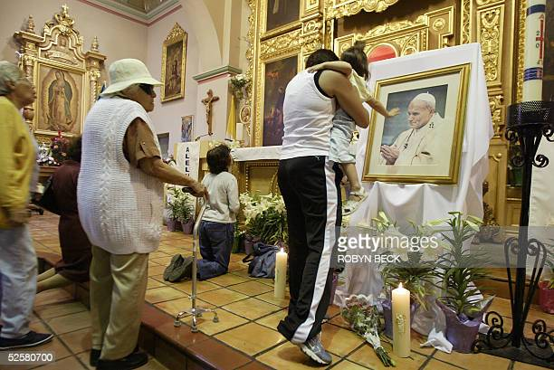 A small girl reaches out to touch a portrait of Pope John Paul II at a special mass said for the pontiff at Our Lady Queen of Angels Church in Los...