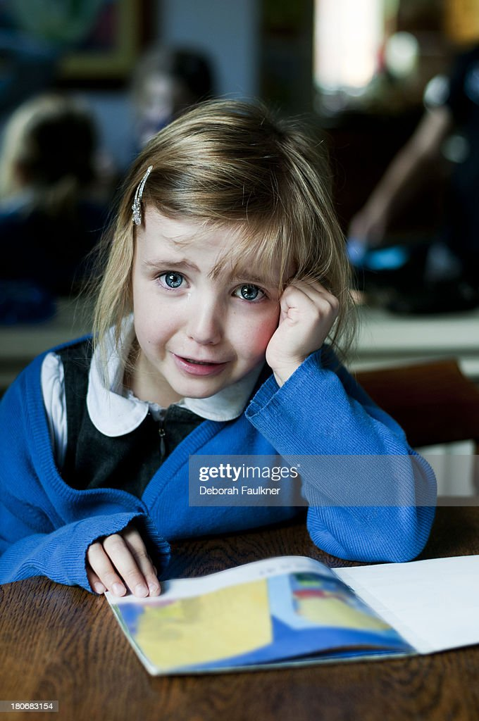 Small girl reading a book and crying : Stock Photo
