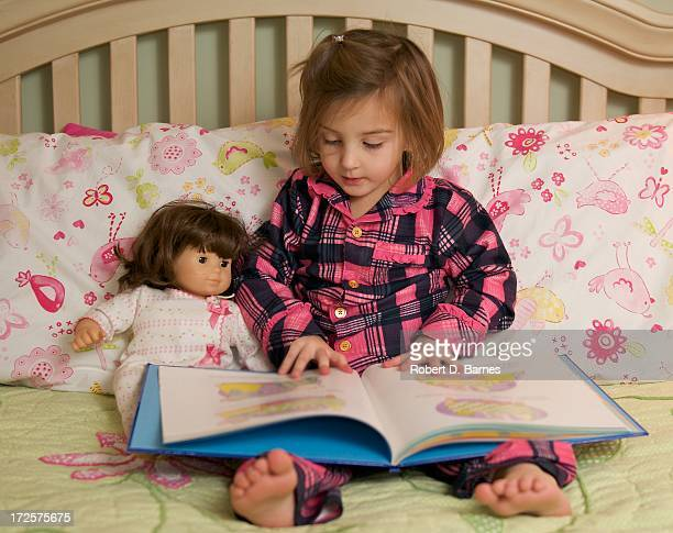 Small girl reading to her doll in bed