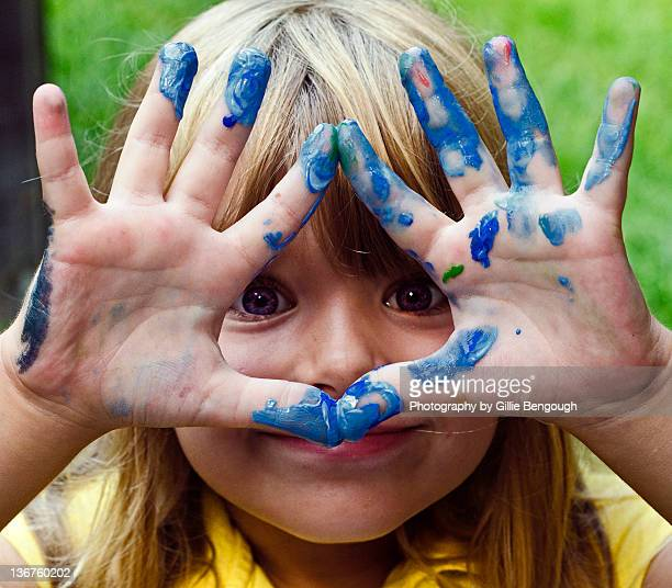 Small girl showing finger painting