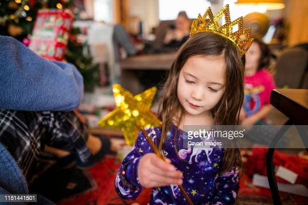 a small girl sits with family at home wearing golden crown and wand - princess stock pictures, royalty-free photos & images