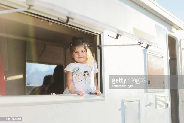 Small girl smiling from campervan's window