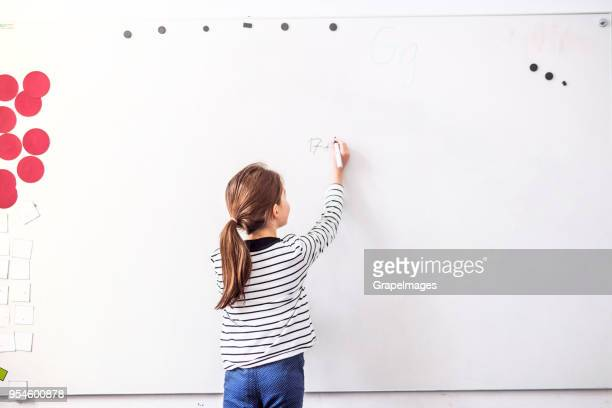 A small girl standing at the whiteboard writing.