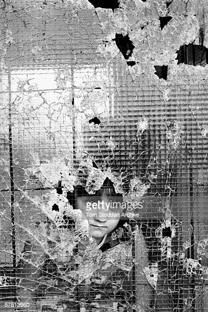 A small girl stares silently through a shattered window as a United Nations aid convoy reaches besieged people in the Sarajevo suburb of Dobrinja