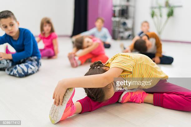 Small girl stretching on a sports training with her friends.