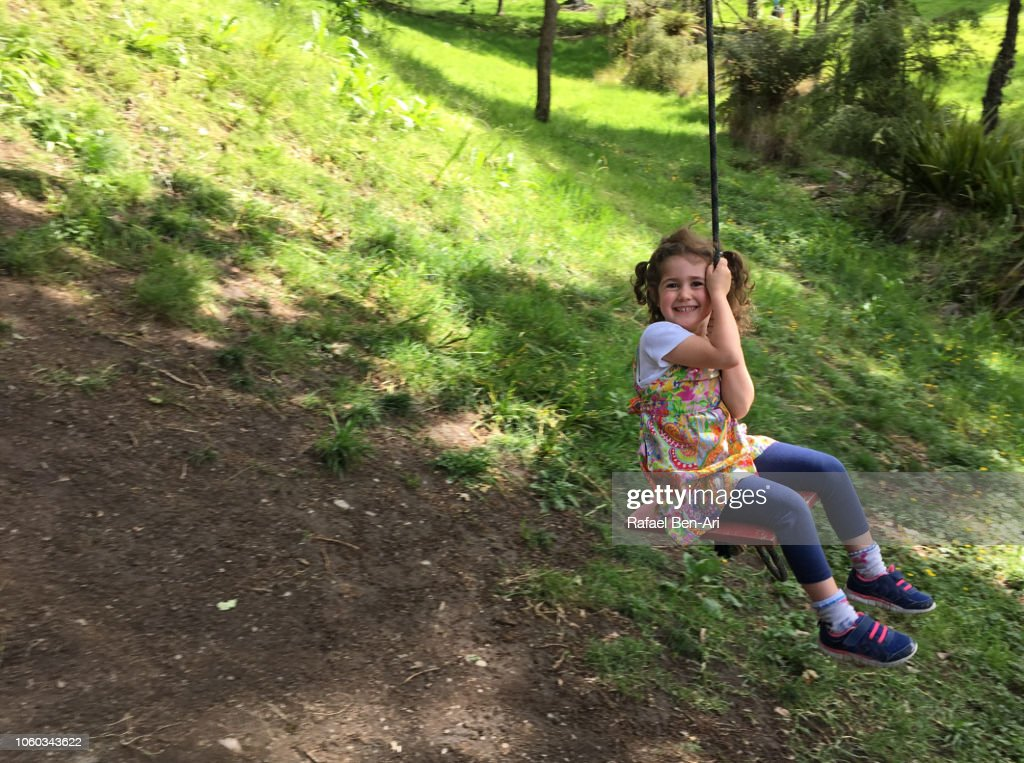 Small Girl Swinging on a Tree Swing : Stock Photo