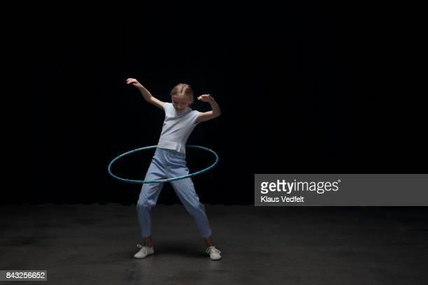 Small girl using hoola hoop, looking down