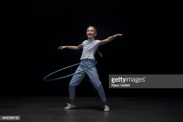 Small girl using hoola hoop, looking up