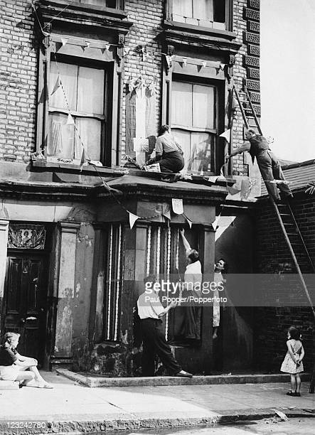 A small girl watches as decorations are hung on the outside of 10 Rillington Place Notting Hill London in preparation for the coronation of Queen...
