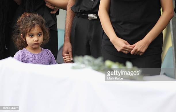 A small girl watches on at a Christian funeral service for the victims of the Christmas Island asylum seeker boat wreck at Castlebrook Memorial Park...