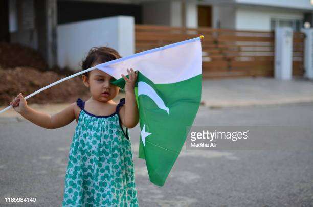 a small girl wearing green frock with pakistan flag in hands on pakistan day independence or national day celebration event. - frock coat stock pictures, royalty-free photos & images