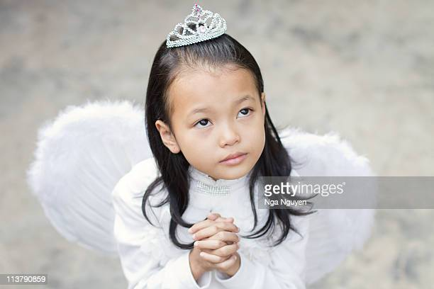 small girl wearing wings and praying - nga nguyen stock pictures, royalty-free photos & images
