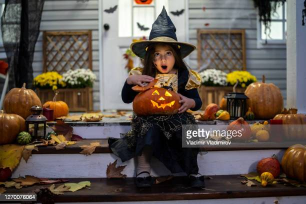 a small girl with a pumpkin lantern - mischief stock pictures, royalty-free photos & images