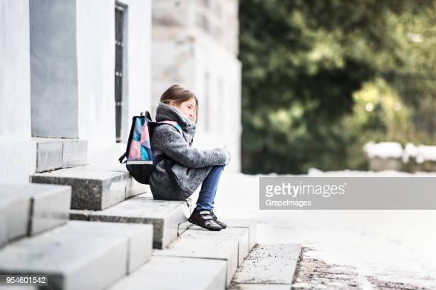 a small girl with a schoolbag sitting on the stairs in front of school. - waiting stock pictures, royalty-free photos & images