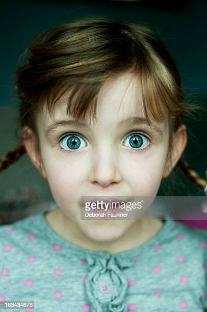 Small girl with plaits looking surprised
