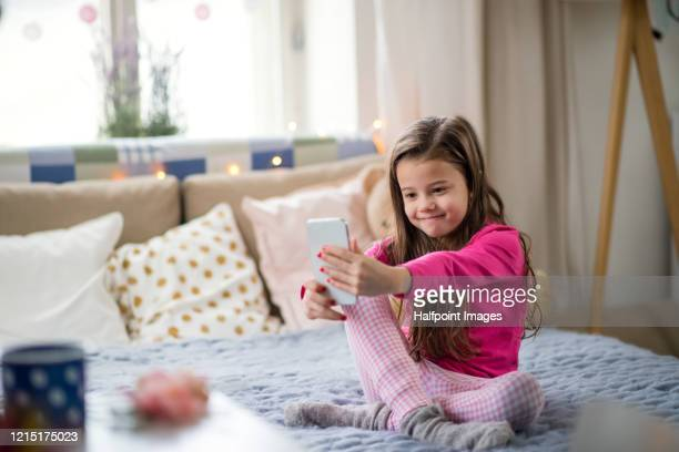 small girl with smartphone sitting on bed, taking selfie. - one girl only stock pictures, royalty-free photos & images